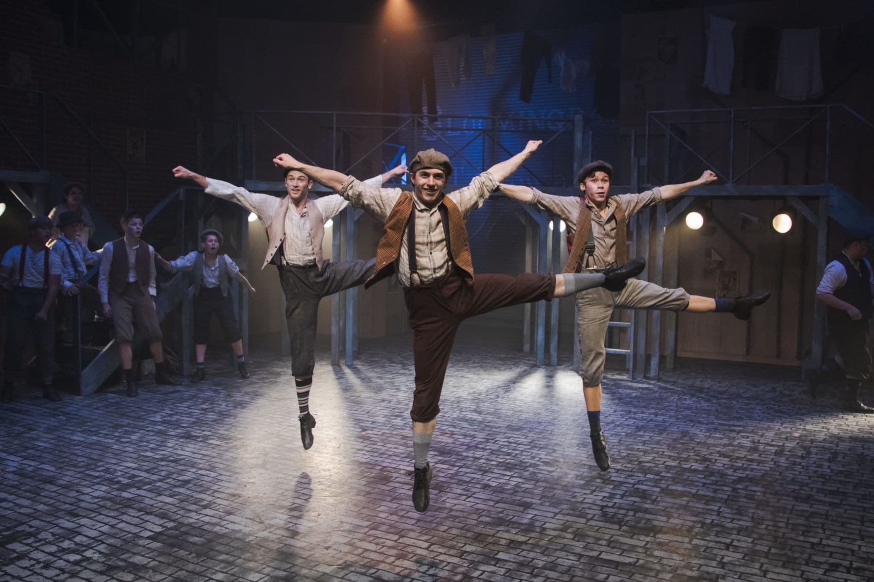 """(L  to R) Zachary Isen as Albert, Tony Wooldridge as Romeo, and Ethan Dea as Race, light up the stage with iconic dance in """"Newsies"""" at Hillbarn Theatre."""
