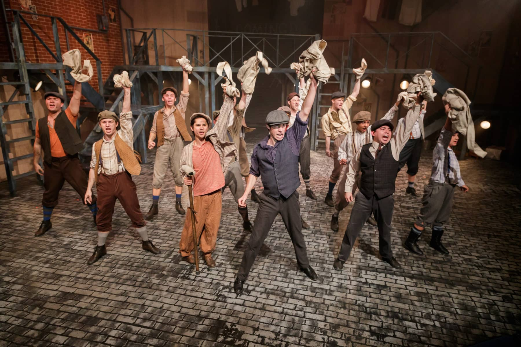 """The Newsies form a union in Newsies Square(L to R) Stephen Kanaski as Crutchie, Kamren Mahaney as Jack Kelly, James Jones as Davey, Noah Itzkovitz as Les, and the rest of the newsboys in """"Newsies"""" at Hillbarn Theatre."""