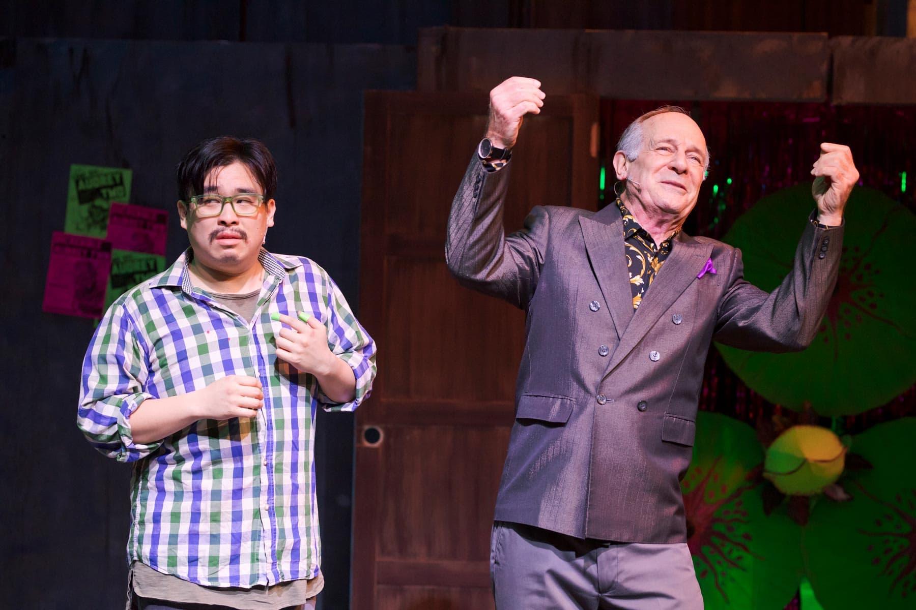 Phil Wong as Seymour and Jesse Caldwell as Mr. Mushnik celebrate Seymour's adoption into Mr. Mushnik's family.