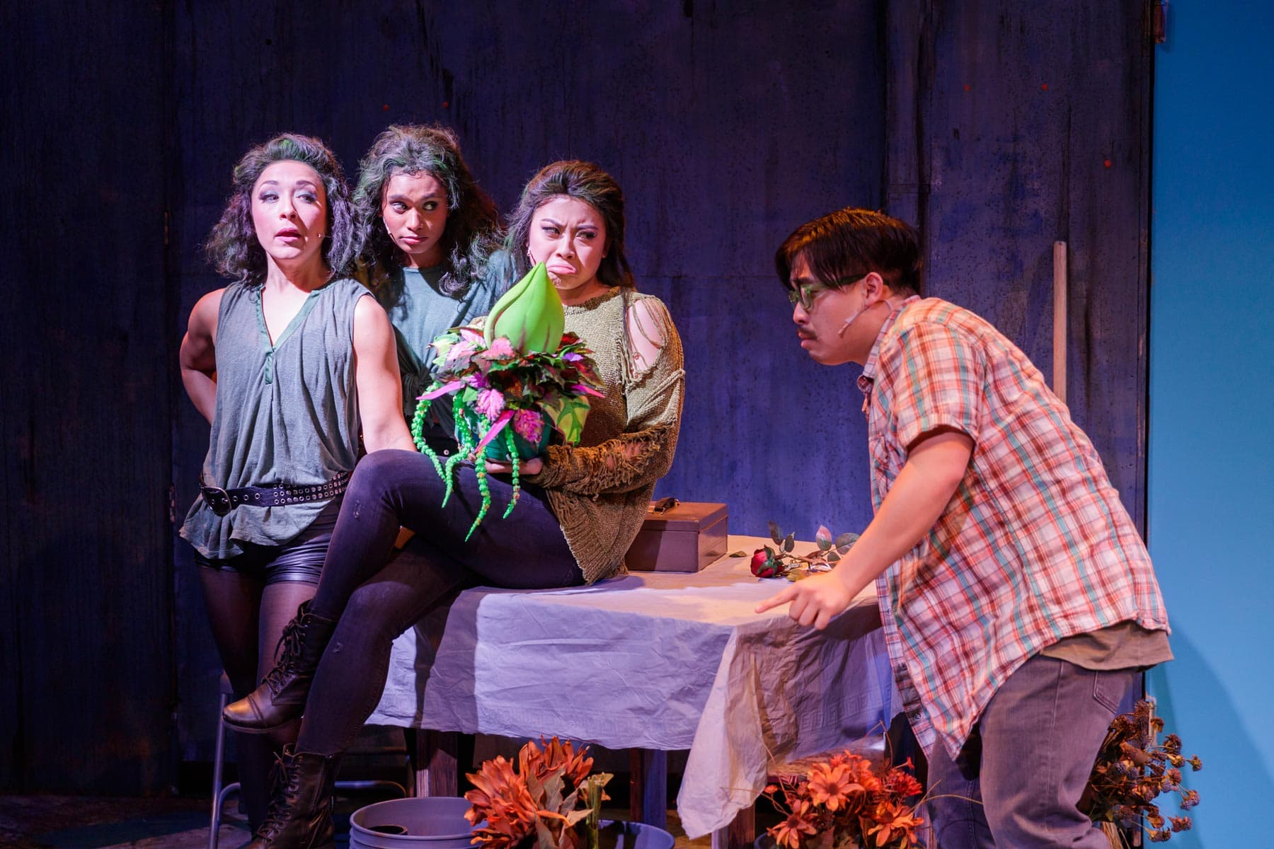 Ronnette (Melinda Campero, Left), Chiffon (Becky Alex, back Center), and Crystal (Kylie Abucay, center) help Audrey II get fed for the first time from Seymore, played by Phil Wong. .
